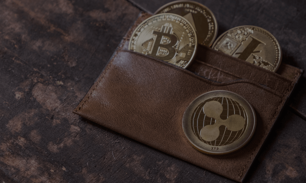 A brown leather wallet with cryptocurrency including bitcoin and ripple inside.